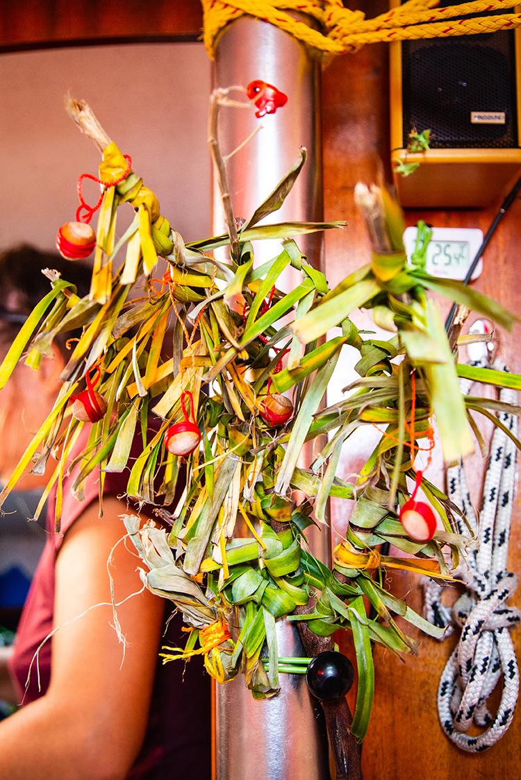 Le sapin de noël Ecodysea : une branche morte et des feuilles de bananiers pour le corps, et des noisettes entourées de fil à surlier rouge pour les boules de noël.